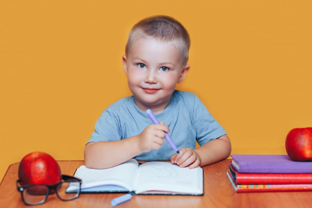 Garotinho, pintando e fazendo trabalhos de casa em sua mesa