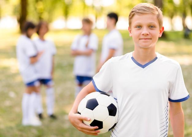 Garotinho posando com uma bola de futebol ao ar livre