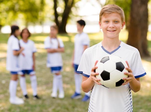 Garotinho posando com uma bola de futebol do lado de fora