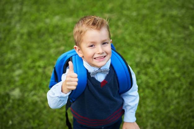 Garotinho pré-escolar feliz com mochila posando ao ar livre