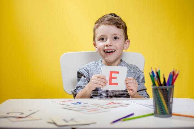 Garotinho pré-escolar sorridente e feliz mostrando cartas em casa fazendo dever de casa