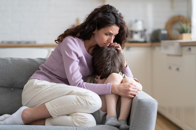 Garotinho recebe proteção do amor materno e apoio mãe acariciando filho filho ofendido chora no sofá