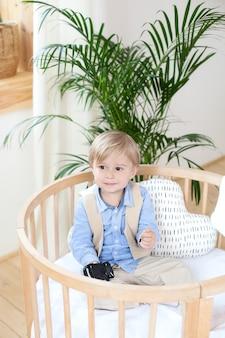 Garotinho. retrato de um menino feliz jogando em um berço. o menino senta-se sozinho em um berço no berçário. bebê solitário fica no berço. waif criança. a criança na cama está sorrindo. quarto infantil interior.
