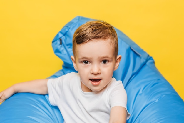 Garotinho rindo em uma parede amarela, sentado em uma cadeira azul.