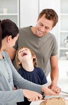 Garotinho rindo enquanto sua mãe cortar pão