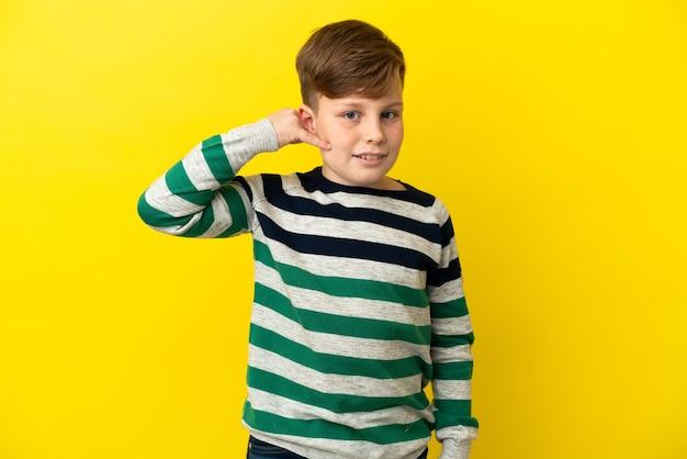 Garotinho ruivo isolado em fundo amarelo, fazendo gesto de telefone. ligue-me de volta sinal