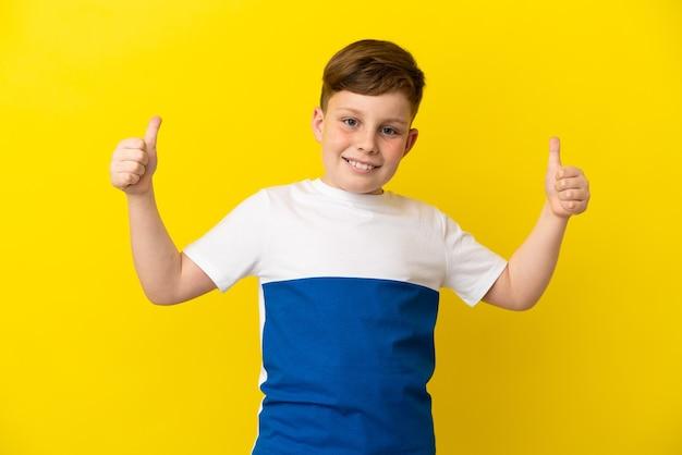 Garotinho ruivo isolado em um fundo amarelo fazendo um gesto de polegar para cima