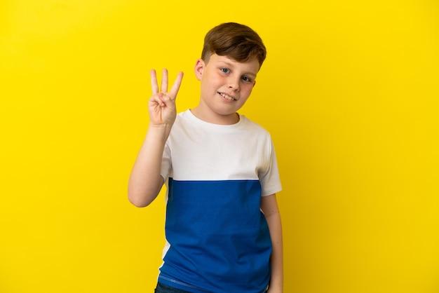 Garotinho ruivo isolado em um fundo amarelo feliz e contando três com os dedos