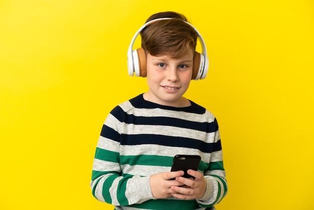 Garotinho ruivo isolado em um fundo amarelo ouvindo música com um celular e olhando para a frente