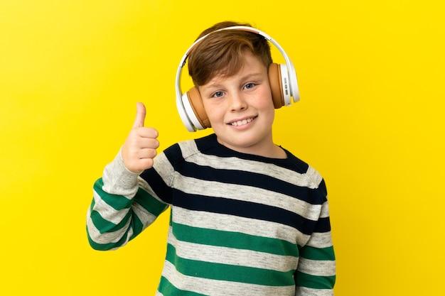 Garotinho ruivo isolado em um fundo amarelo ouvindo música e com o polegar para cima