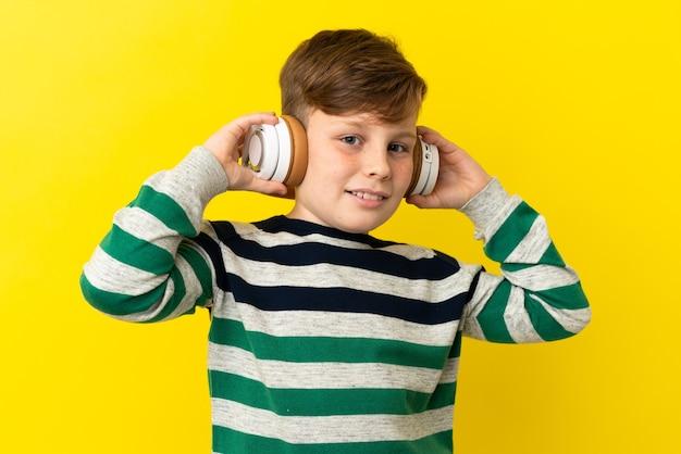 Garotinho ruivo isolado em um fundo amarelo ouvindo música