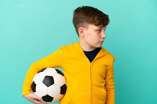 Garotinho ruivo isolado em um fundo azul com uma bola de futebol