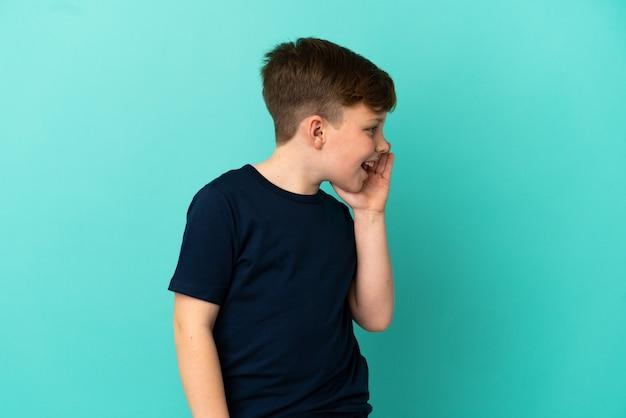 Garotinho ruivo isolado em um fundo azul gritando com a boca bem aberta para o lado
