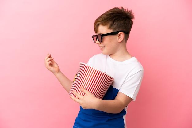 Garotinho ruivo isolado em um fundo rosa com óculos 3d e segurando um grande balde de pipocas enquanto olha para o lado