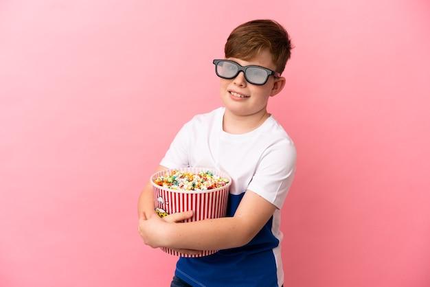 Garotinho ruivo isolado em um fundo rosa com óculos 3d e segurando um grande balde de pipocas