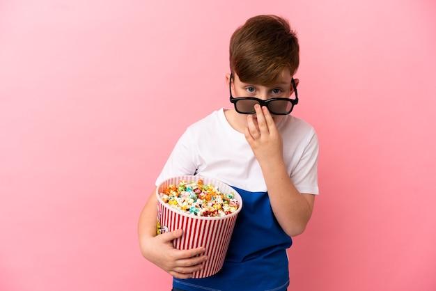 Garotinho ruivo isolado em um fundo rosa surpreso com óculos 3d e segurando um grande balde de pipocas