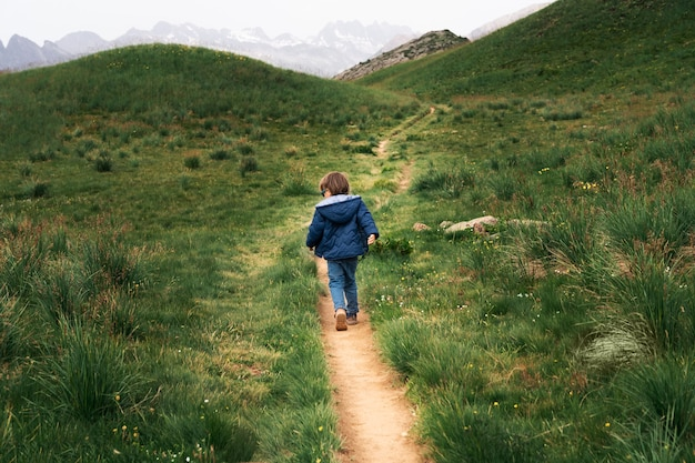 Garotinho runnig em um caminho no alto das montanhas. caminhadas com o conceito de crianças.