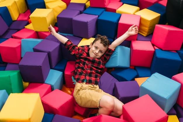 Garotinho se divertindo com cubos coloridos suaves no centro de entretenimento infantil. infância feliz