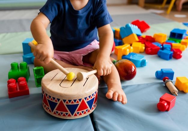 Garotinho se divertindo e tocando tambor de brinquedo de madeira