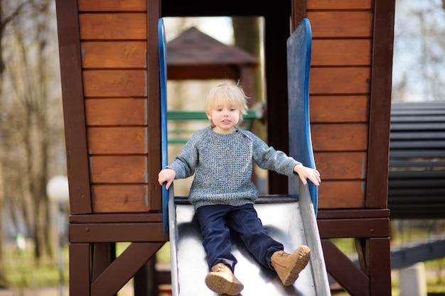 Garotinho se divertindo no playground ao ar livre / no slide