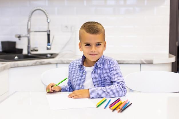Garotinho se senta em uma mesa em uma cozinha brilhante e desenha com lápis