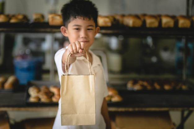 Garotinho segurando a loja de padaria de fundo de papel de saco