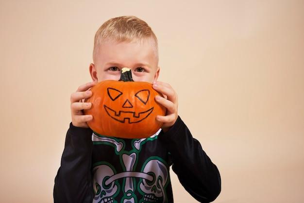 Garotinho segurando abóbora de halloween na frente do rosto