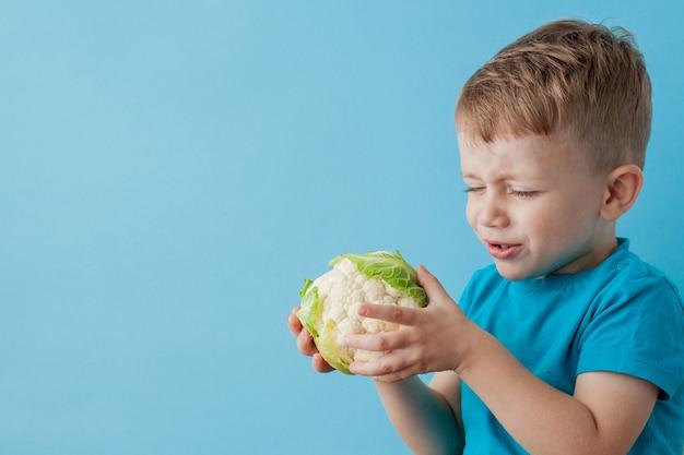 Garotinho segurando brócolis nas mãos sobre fundo azul, dieta e exercício para o conceito de boa saúde
