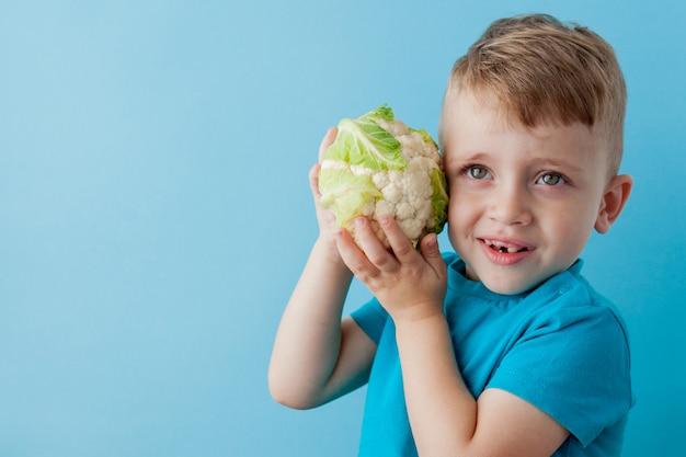 Garotinho segurando brócolis nas mãos sobre fundo azul, dieta e exercícios para o conceito de boa saúde