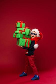 Garotinho segurando caixas de presente de natal