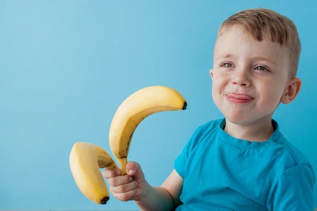 Garotinho segurando e comendo uma banana sobre fundo azul, comida, dieta e conceito de alimentação saudável