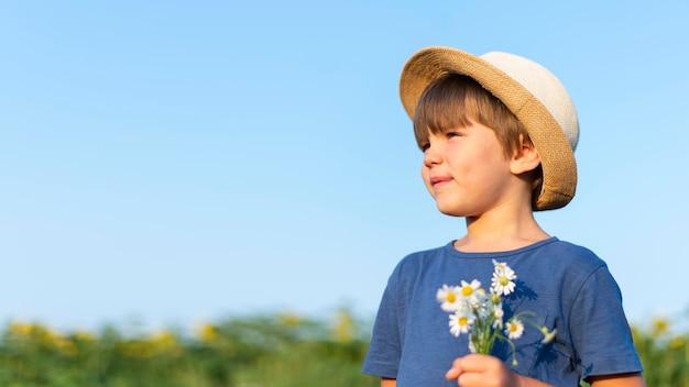 Garotinho segurando flores