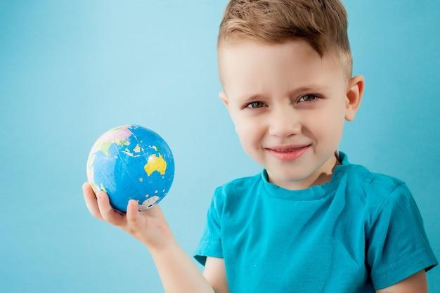 Garotinho segurando um globo em fundo azul