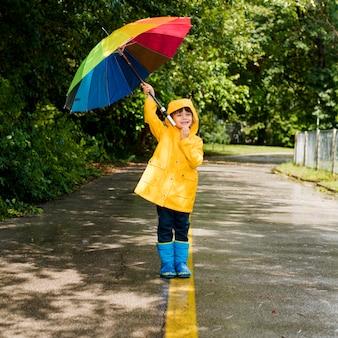Garotinho segurando um guarda-chuva acima da cabeça