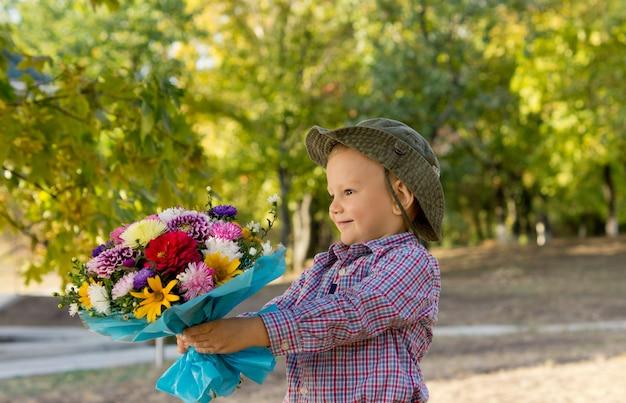 Garotinho segurando um lindo buquê de flores embrulhado para presente com o braço estendido enquanto o apresenta para sua mãe