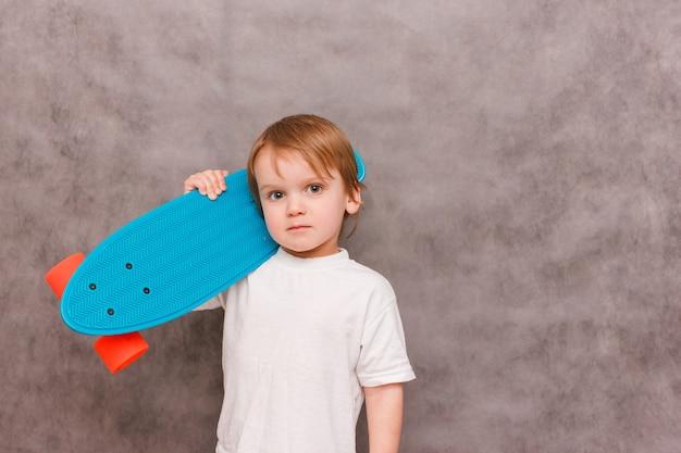 Garotinho segurando um skate no ombro