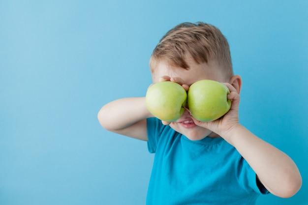 Garotinho segurando uma maçã nas mãos sobre azul, dieta e exercícios para uma boa saúde
