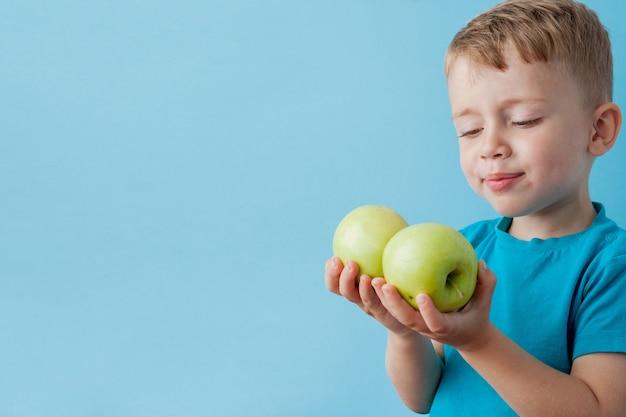 Garotinho segurando uma maçã nas mãos sobre fundo azul, dieta e exercício para o conceito de boa saúde