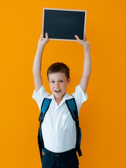 Garotinho segurar lousa escolar sobre fundo amarelo. pequeno uniforme escolar de aluno com uma mochila com as mãos em branco. quadro-negro para anúncio, copie o espaço. pela sua atenção.