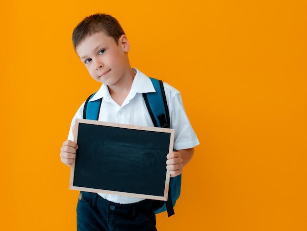 Garotinho segurar lousa escolar sobre fundo amarelo. pequeno uniforme escolar de aluno com uma mochila com as mãos em branco.