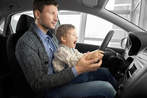 Garotinho sentado com o pai no banco do motorista no carro novo.