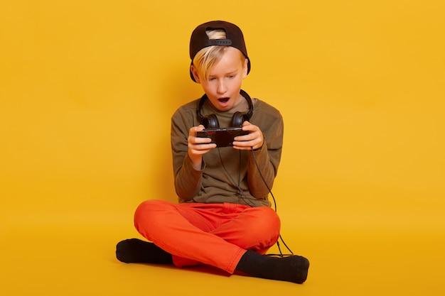 Garotinho sentado com smartphone, cara vestindo casualmente com fones de ouvido no pescoço, posando com a boca aberta e parece animado, criança com as pernas cruzadas, segurando o telefone móvel nas mãos.