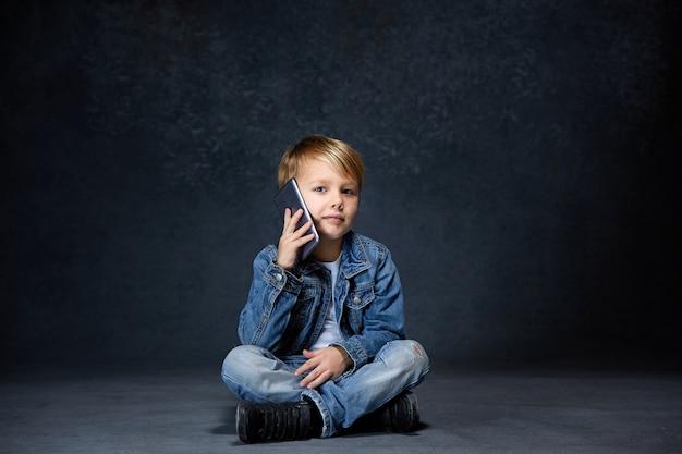 Garotinho sentado com smartphone em estúdio