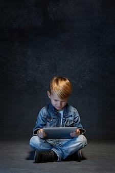 Garotinho sentado com um tablet no estúdio