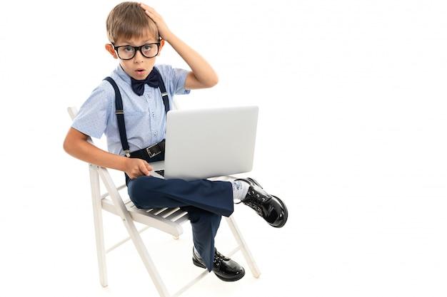 Garotinho sentado em uma cadeira com um laptop no colo em uma parede branca