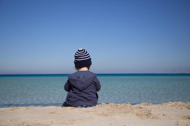 Garotinho sentado em uma praia, vista traseira