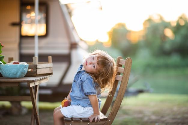 Garotinho sentado na cadeira no piquenique em família
