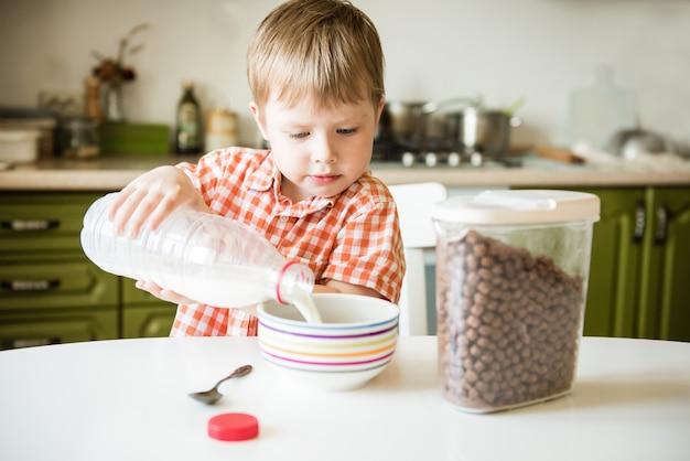 Garotinho sentado na cozinha, tomando café da manhã, servindo leite em uma xícara de cereal, preparando uma refeição saudável e saborosa