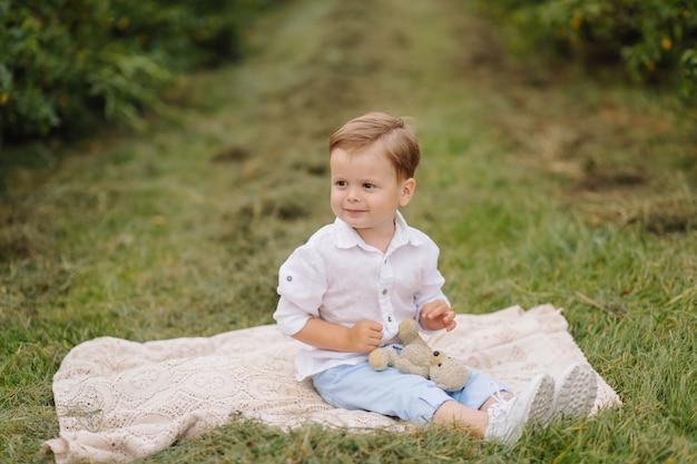 Garotinho sentado na manta de piquenique no jardim da casa