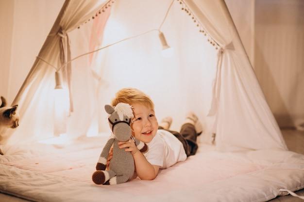 Garotinho sentado na tenda aconchegante com luzes em casa no natal